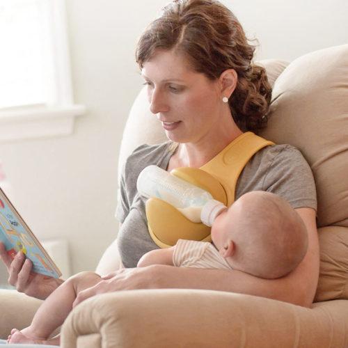 מחזיק בקבוק אכילה לתינוק על כתף ההורה